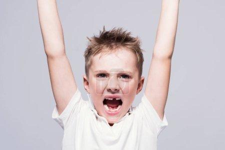 Photo pour Petit garçon hurlant sans dents en colère dans un T-shirt blanc avec les bras levés sur un fond clair . - image libre de droit