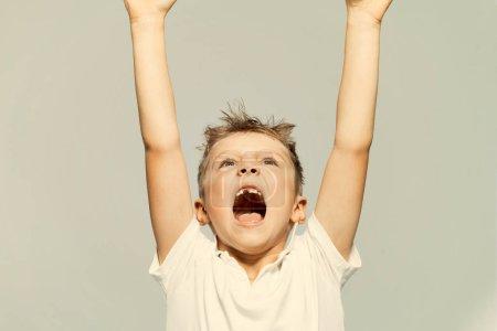 Photo pour Petit garçon sans dents à la bouche ouverte leva les mains. Fond clair - image libre de droit