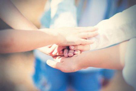 Photo pour Un groupe de filles enfants marchant dans la forêt d'été ont mis leurs mains ensemble. Le concept d'amitié et d'unité. Esprit d'équipe . - image libre de droit