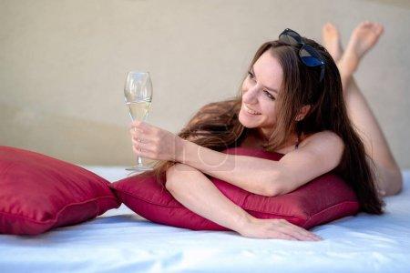 Photo pour La jeune femme sexy riante dans le bikini se trouve avec un verre de vin mousseux dans le salon qui est observable et donne un toast - image libre de droit