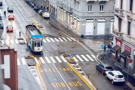 Photo for Milan. Italy - May 19, 2019: Street Panorama in Milan with Tram after Rain. Aerial View. Pedestrians and Cars on a Cloudy Day. Bus, Taxi and Tram Lane Traffic Signs on a Street. - Royalty Free Image