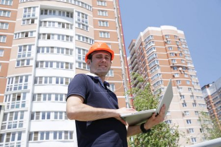 Photo for Portrait of a young handsome man in a protective helmet with a laptop in his hands in front of a high building. Construction, architecture and business. - Royalty Free Image