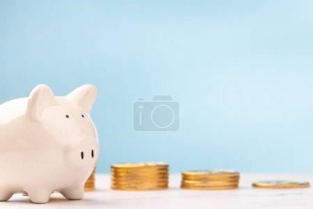 Foto de Linda alcancía con monedas de oro en la mesa blanca y fondo azul. ahorro concepto de dinero . - Imagen libre de derechos