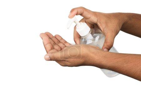 Photo pour La main de l'homme pompe de l'alcool, un gel d'une bouteille, pour nettoyer ses mains du coronavirus sur fond blanc . - image libre de droit
