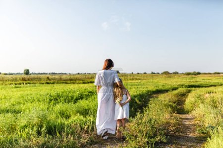 rear view of mother and daughter standing on path in green meadow