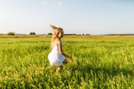 adorable little child running by green field under sunset rays