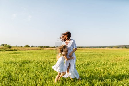 Photo for Mother and daughter having fun together and embracing in green meadow on windy day - Royalty Free Image