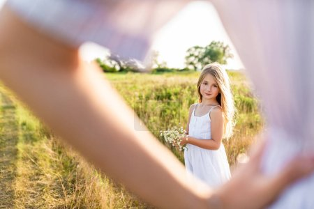 beautiful little girl with field flower bouquet looking at mother standing blurred on background in green meadow