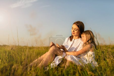 Photo for Mother and daughter sitting on green grass on sunset - Royalty Free Image