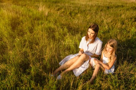 mother and daughter sitting on green grass and looking at sunset