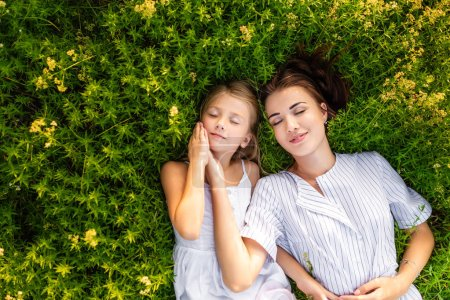 top view of happy mother and daughter relaxing while lying in flowery meadow