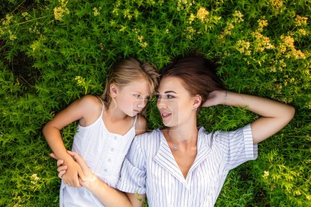 top view of mother and daughter relaxing while lying in flowery meadow and looking at each other