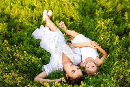 Photo for Happy mother and daughter relaxing while lying in flowery meadow - Royalty Free Image