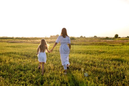 rear view of mother and daughter in white dresses holding hands and running in green meadow on sunset