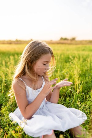 adorable little child sitting on green grass and looking at hand under sunset rays