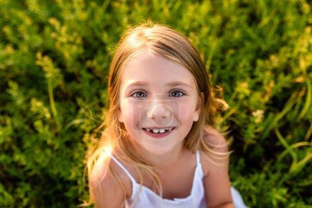 Photo pour Portrait en gros plan d'adorable petit enfant regardant la caméra sur l'herbe verte sous les rayons du coucher du soleil - image libre de droit
