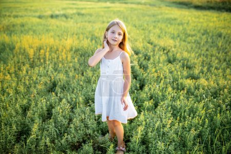 cute little child in white dress posing on field and looking at camera