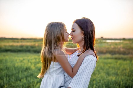 close-up portrait of beautiful mother and daughter embracing and touching noses in green field on sunset