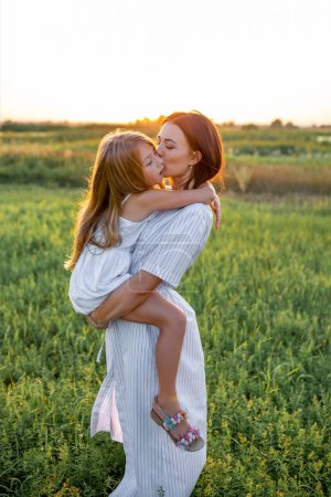 mother and daughter embracing in green field on sunset