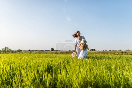 Photo for Beautiful smiling mother and daughter playing in green meadow - Royalty Free Image