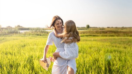 beautiful happy mother and daughter embracing in green field on sunset