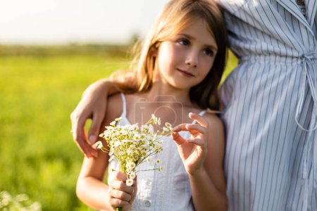 cropped shot of mother embracing daughter while she holding field flowers bouquet in green meadow