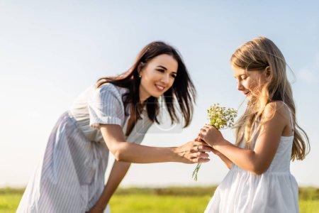 Foto de Madre dando el ramo de flores de campo a hija en prado verde - Imagen libre de derechos