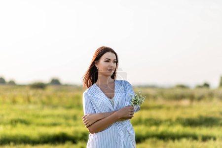 Photo pour Attrayant jeune femme avec bouquet de fleurs de champ sur champ vert sous les rayons du coucher du soleil - image libre de droit