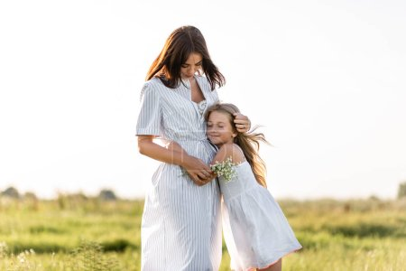 Photo pour Mère et fille heureuse embrassant dans la prairie verte - image libre de droit