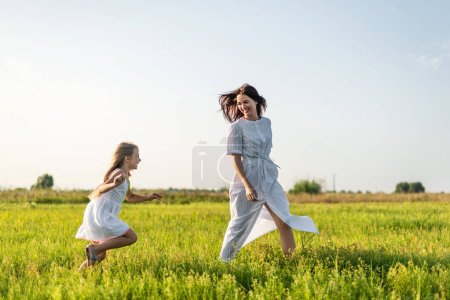 Photo for Mother and daughter having fun in green meadow together - Royalty Free Image