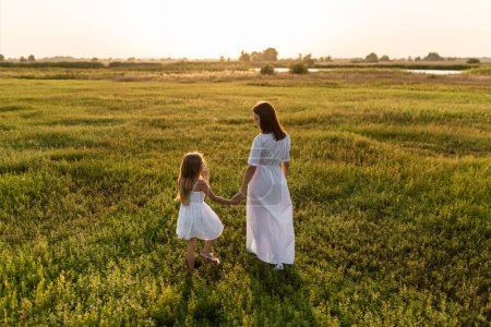 rear view of mother and daughter walking in green meadow in evening