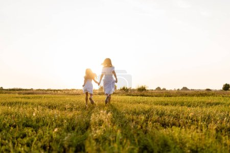 Photo for Rear view of mother and daughter running in green field with sunset on background - Royalty Free Image