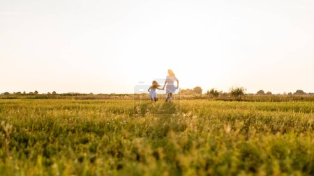 Photo for Rear view of mother and daughter running in green meadow with sunset on background - Royalty Free Image