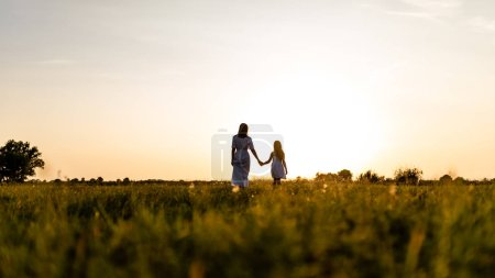 Photo for Rear view of mother and daughter walking in green field with sunset on background - Royalty Free Image