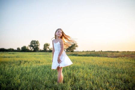 adorable little child in white dress posing on field on sunset