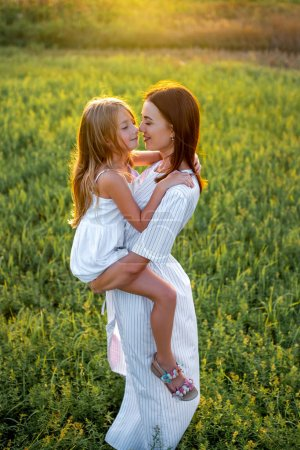 Photo for High angle view mother and daughter embracing in green meadow - Royalty Free Image
