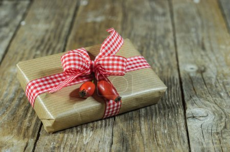 Photo for Gift with red ribbon and rose hip decoration on wooden table background - Royalty Free Image