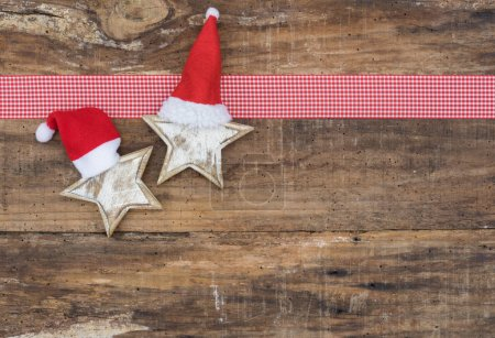 Photo for Two Christmas stars with santa claus caps with checkered ribbon frame on wooden backdrop, copyspace - Royalty Free Image