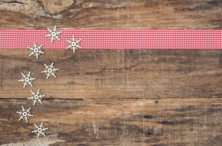 Photo for Christmas snowflake ornaments with red ribbon border on rustic wooden background - Royalty Free Image