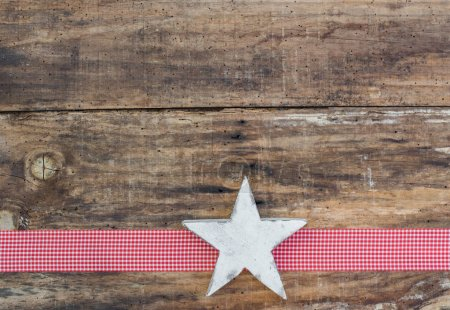 Photo for Christmas star ornament on red ribbon border decoration and rustic wooden background, copyspace - Royalty Free Image