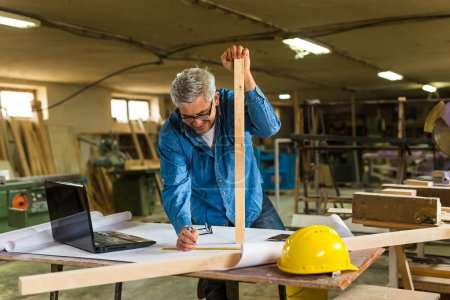 Photo for Mature carpenter working in workshop - Royalty Free Image