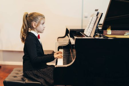 Photo for Pretty little girl learning playing piano - Royalty Free Image