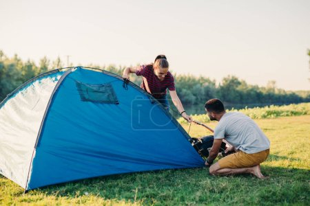 Photo for Friends preparing tent for camping outdoor - Royalty Free Image