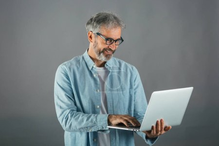 Photo for Studio shot of middle aged man using computer - Royalty Free Image