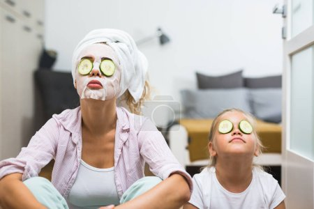Photo for Mother and daughter applying cosmetic face mask at home - Royalty Free Image