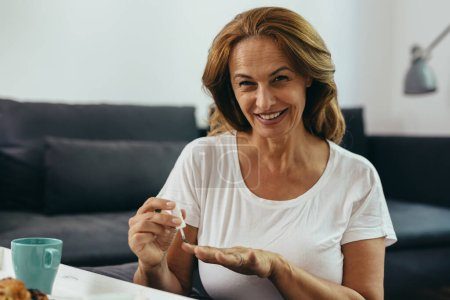 Photo for Middle aged woman polishing nails at her home - Royalty Free Image