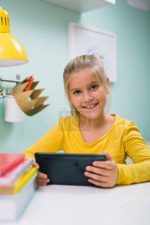 Photo pour Fille en utilisant tablette ordinateur assis table dans sa chambre - image libre de droit