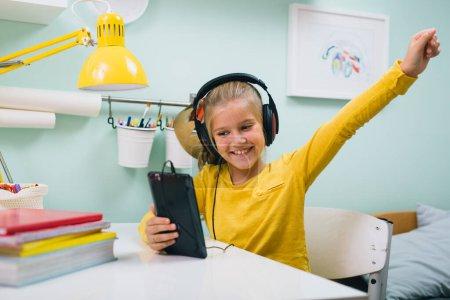 Photo pour Fille en utilisant tablette écouter de la musique sur écouteurs assis table dans sa chambre - image libre de droit