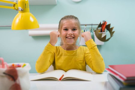 Photo for Front view of schoolgirl sitting table at her room - Royalty Free Image