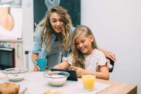 Photo for Mother and daughter using tablet while having breakfast - Royalty Free Image
